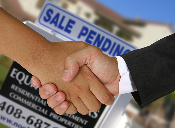 Two real estate professionals shaking hands