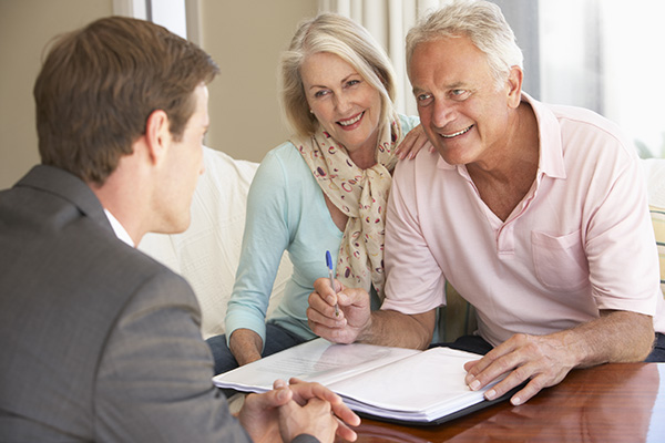 Attractive Baby Boomer couple reviewing paperwork with male realtor