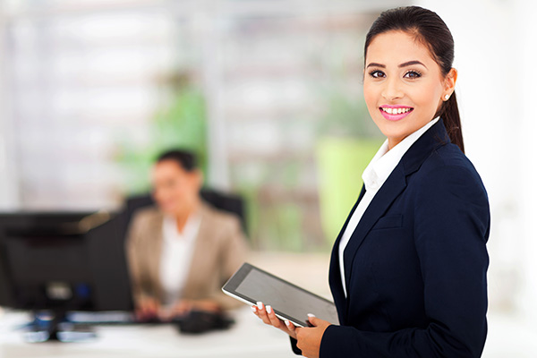 Woman REALTOR holding an iPad and turning to smile at the camera