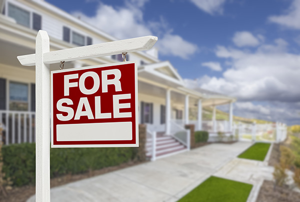 For Sale sign posted in front of a house with stairs leading to a wraparound porch