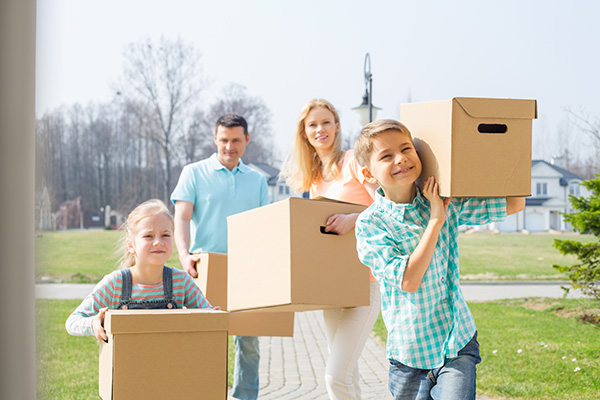 Mom, dad and two kids carrying boxes into their new home