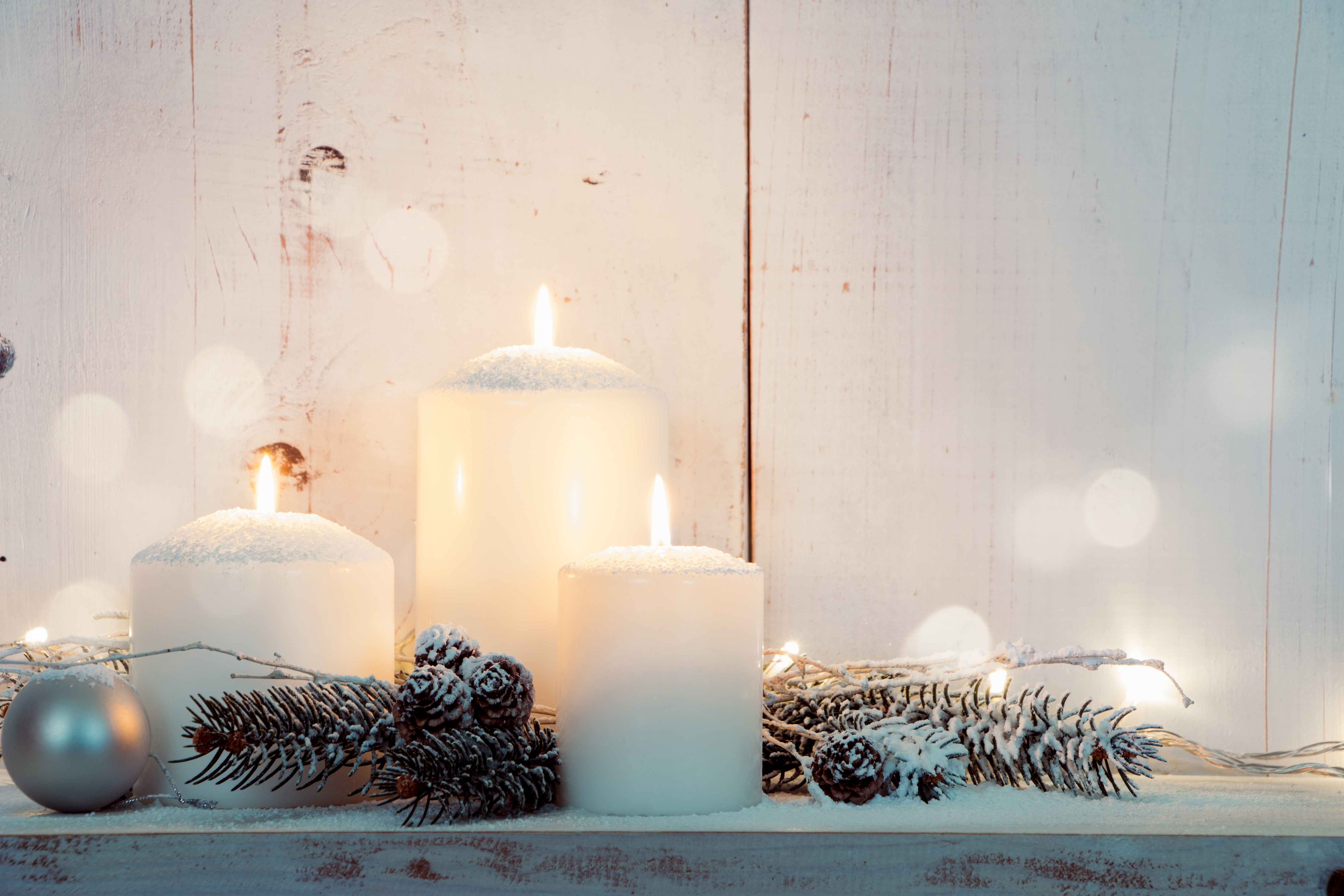 White pillar candles surrounded by snow covered pinecones